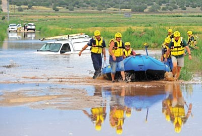 Matt Hinshaw/The Daily Courier<br>Members of the Chino Valley Fire District's Technical Rescue team pull an unidentified man to safety after rescuing him from his flooded utility work truck Monday afternoon on Sweet Valley Road in Paulden.