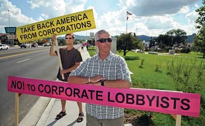 Brett Soldwedel/The Daily Courier<br> David Rutherford, left, and Jon Lewis protest corporate influence on government in a demonstration at Veterans Memorial Park on Tuesday.
