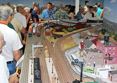 Courtesy photo<br> Model train enthusiasts get a close look at a model train layout at the home of Paulden resident Peter Atonna last summer during the Central Arizona Model Train Club's home tour.