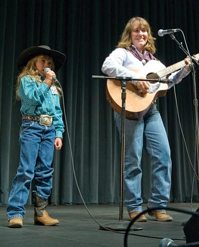 Les Stukenberg/The Daily Courier<br> Eight-year-old Cora Rose and Laurie Wood perform at the 2009 Arizona Cowboy Poets Gathering.