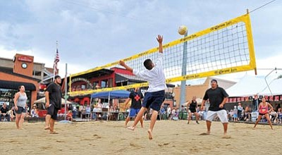 Matt Hinshaw/The Daily Courier<br>Team Juju and Team Sand Sharks face off against each other on Goodwin Street during a game of beach volley at the first Firehouse Luau in downtown Prescott this past July 17.
