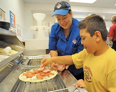 Matt Hinshaw/The Daily Courier<br> Nadine McGee, general manager of Domino's in Prescott, works with Taylor Hicks student Ayden Torres, 8, on building a pizza Thursday morning.