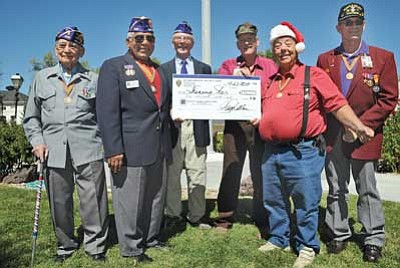 Brett Soldwedel/The Daily Courier<br>Pictured from left are Dr. John Reyna Tapia, Alfonso Santillan Jr., Hugh Branigan, Charles Butkewicz, Dennis Spicknell and Jim Burg. Spicknell, of Shining Star, is receiving a $3,688 donation from the Military Order of the Purple Heart to help fund batteries for the motorized scooters he refurbishes and donates to local area veterans.