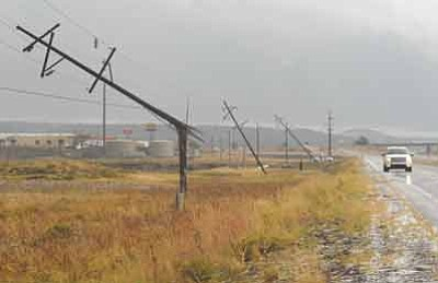 Josh Biggs/Arizona Daily Sun, AP<br>Broken power poles line a frontage road along I-40 near Bellemont, where several tornadoes touched down on Wednesday.