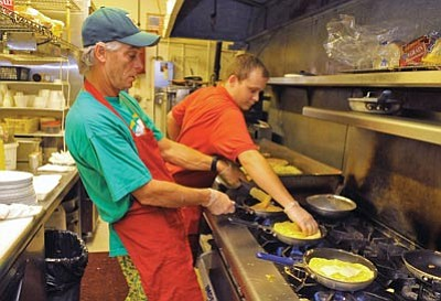 "Matt Hinshaw/The Daily Courier<br> SueAnn's Apple Pan owner Mark Duncan and Head Cook Matt Schumaker work together making omelets Friday evening during the ""PJ's & Eggs"" fundraiser to benefit Arizona's Children Association foster care programs"