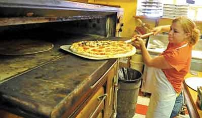 Matt Hinshaw/The Daily Courier<br>Ashlee Elkins, manager of Bill's Pizza, pulls a pizza out of the oven Tuesday afternoon in Prescott.