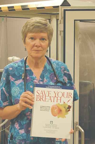 Ken Hedler/The Daily Courier<br>Elizabeth Page, a respiratory therapist at Yavapai Regional Medical Center in Prescott, displays a copy of a spiral-bound book that she wrote for people who suffer from chronic obstructive pulmonary disease.
