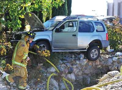 Les Stukenberg/The Daily Courier<br>A Central Yavapai firefighter moves around one of of the two vehicles involved in a collision at the intersection of Centre Court and Glassford Hill Road Monday afternoon. Emergency personnel flew one person to Flagstaff Regional Medical Center.