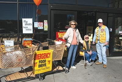 Courtesy photo<br> Audrey and Len Covello (seated), along with Earl Donnels, welcomed shoppers to the Safeway store off Willow Creek Road, one of five stores that participated in the food drive.