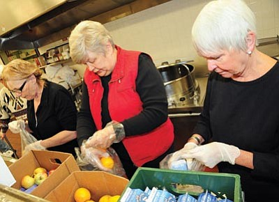 Brett Soldwedel/The Daily Courier<br>Volunteers Eula Parish, left, Marcy Lage and Judy Lauver pack food on Thursday for underprivileged PUSD students to take home on weekends.
