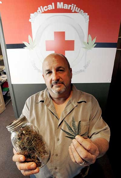Ross D. Frankin/The Associated Press<br> Allan Sobol, operations manager at Marijuana Marketing Strategies, LLC, who runs the Medical Marijuana Dispensary, stands in his store while holding up replica samples of marijuana Nov. 3 in Phoenix.