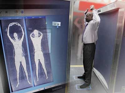 The Associated Press<br> A security officer demonstrates the full-body scanner at the Orlando, Fla., airport.