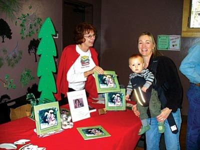 """Highlands Center/Courtesy photo<br> Author Connie Johnson, left, shares one of her children's books with a patron during a past """"Warmth from the Heart"""" Holiday Arts & Crafts festival at the Highlands Center for Natural History. This year's festival will run from 9 a.m.–3 p.m. Saturday."""