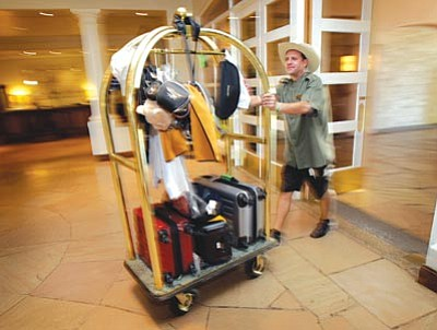 Matt York/The Associated Press<br> In this photo taken on Oct. 14, David Dumyahn, a bellhop of at the Fairmont-Scottsdale Princess Resort in Scottsdale, brings in luggage for guests. A boycott of Arizona in the wake of a controversial immigration law has cost the state more than $140 million in lost meeting and convention business, a new report released Thursday shows.