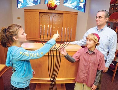 Brett Soldwedel/The Daily Courier<br>Bailee Petrovsky, 12, and Derek Watkins, 12, both light candles on the Menorah in preparation for Hanukkah as Rabbi William Berkowitz looks on at Temple B'rith Shalom.