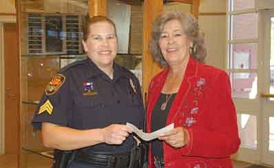 Deniece McAnulty/Courtesy photo<br>Deniece McAnulty, right, president of the Granite Mountain Riders, presents a check for $500 for the Shop with a Cop program to Sgt. Amy Bonney, community section supervisor for the Prescott Police Department.