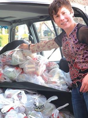 Courtesy photo<br> Julie Meyers, weekend family food coordinator for The Coalition for Compassion and Justice, loads up her car with food boxes to deliver to children in the Prescott area.