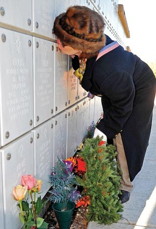 Matt Hinshaw/The Daily Courier<br> Sandee Hanahan kisses the niche that houses her husband's remains after laying a wreath at the Prescott National Cemetery Saturday morning during the Wreaths Across America ceremony. Hanahan's husband Thomas passed away a year ago and served his country in the United States Navy.