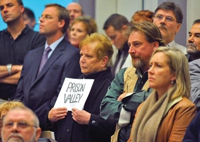 "Matt Hinshaw/The Daily Courier, file photo<br> A Prescott Valley resident makes her stance clear with a sign that reads ""Prison Valley"" during a January 2010 Town Council meeting in Prescott Valley. Representatives from Elliot D. Pollack and Co. discussed the economic impact that a proposed private prison could have on Prescott Valley."