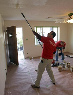 Matt York/The Associated Press<br> Allan Bernstein, a volunteer from the Honeywell Aerospace Human Resources Department, paints the ceiling during a month-long renovation of a donated home in Phoenix.