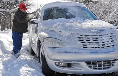 Matt Hinshaw/The Daily Courier<br> John McCormick cleans off his windshield after digging his car out of the snow Dec. 30 in Prescott.