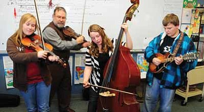 Les Stukenberg/The Daily Courier<br>Heritage Middle School music teacher Kent Gugler watches as former student Cheyenne Jasper, at left, along with current students Kylee Driescher and Matt Haynes practice a tune that they will play to try out for the Cultural Arts Conservatory in conjunction with the Sharlot Hall Museum.