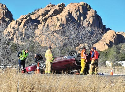 Les Stukenberg/The Daily Courier<br>Emergency personnel wait for a tow truck to arrive at the scene of a one-vehicle rollover on Highway 89 near the entrance to the Phippen Museum in Prescott Monday morning. Lifeline Ambulance transported one person to Yavapai Regional Medical Center with what was believed to be non-life threatening injuries.
