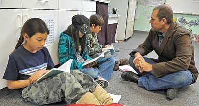 Matt Hinshaw/The Daily Courier<br>David McNelly, lead teacher at La Tierra Community School, listens to, from left, Dakota McConnell, 10, Abby Lugo, 11, and Taban Wall, 10, read together Thursday morning in Prescott.