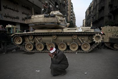 Tara Todras-Whitehill/The Associated Press<br> An Egyptian Muslim cleric cries in front of on army tank in Tahrir, or Liberation square, in Cairo, Egypt on Wednesday. Several thousand supporters of President Hosni Mubarak, including some riding horses and camels and wielding whips, clashed with anti-government protesters Wednesday as Egypt's upheaval took a dangerous new turn.