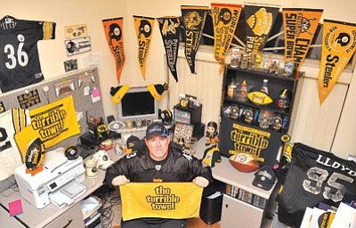 Matt Hinshaw/The Daily Courier<br> Lifelong Pittsburg Steelers fan and AZ Adrenaline defensive coordinator Kurt Dembaugh shows off his Steelers shrine Thursday night at his home in Prescott Valley.