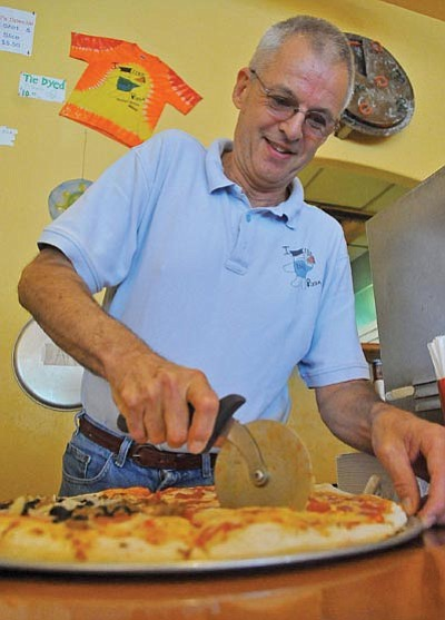 Matt Hinshaw/The Daily Courier<br>Bill Tracy, owner of Bill's Pizza, slices up a freshly baked pizza.