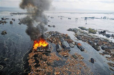 Houses swallowed by tsunami waves burn in Natori, Miyagi Prefecture (state) after Japan was struck by a strong earthquake off its northeastern coast Friday, March 11, 2011. (AP Photo/Kyodo News)