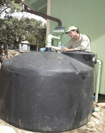 The Daily Courier file photo<br> MacRae Nicoll, owner of High Desert Rain, puts a second coat of paint on a 550-gallon rainwater catchment system at a Prescott home in 2007.