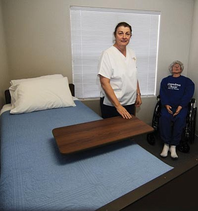 Les Stukenberg/The Daily Courier<br>Sherril Longmuir, owner of Yavapai Healthcare Academy, a certified nursing assistant school, shows one of the two simulated hospital rooms that students use at the school. A mannequin named Grandma Chase sits in the corner.