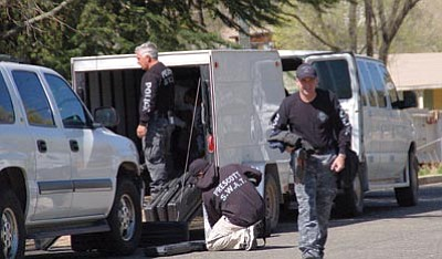 Lisa Irish/The Daily Courier<br /><br /><!-- 1upcrlf2 -->Prescott police pack up their gear Wednesday morning after a man allegedly brandished a handgun at a neighbor and then barricaded himself in his own trailer at the DownTown Trailer Park at 420 S. Montezuma St.<br /><br /><!-- 1upcrlf2 --><br /><br /><!-- 1upcrlf2 --><br /><br /><!-- 1upcrlf2 -->