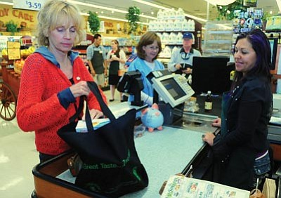 Les Stukenberg/The Daily Courier<br>Jeanne Landstad bags her groceries in a reusable bag as the New Frontiers grocery store in Prescott will soon stop using plastic bags to bag groceries.
