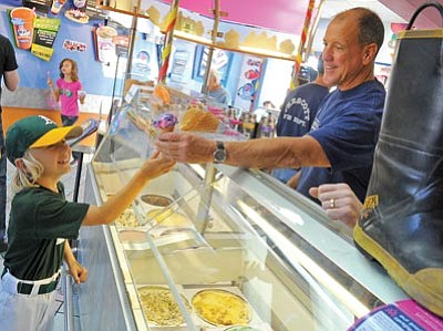 Matt Hinshaw/The Daily Courier<br> Prescott firefighter Mark Matthews hands Maxwell Day, 8, a cotton-candy-flavored ice cream cone Wednesday evening during Baskin Robbins' 31-Cent Scoop Night fundraiser.