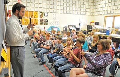 Matt Hinshaw/The Daily Courier<br> Abia Judd Music Teacher Caleb Doyel shows a class the correct finger positions for a note on the recorder Tuesday morning in Prescott. Doyel was recently named the 2011 Yavapai County Outstanding First-Year Teacher.