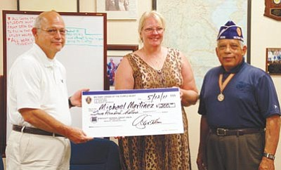 Lisa Irish/The Daily Courier<br> Larry and Sharon Martinez accept a check Thursday for $200 for their son U.S. Marine Corps Lance Cpl. Michael Martinez from a local Wounded Warrior Program that was recently started up by the Military Order of the Purple Heart Major. John R. Tapia Ph.D. Chapter #608's Commander Sgt. Alfonso Santillan Jr., (Ret).
