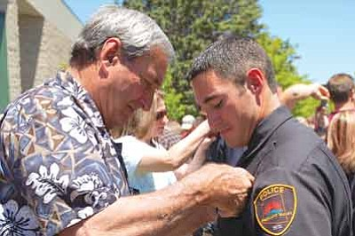 Lisa Irish/The Daily Courier<br>Buzz Fournier, left, pins a Prescott Valley Police Department badge on his youngest son Nick, a newly sworn-in reserve officer, Thursday outside the Yavapai College Performance Hall. Nick, a Central Yavapai Fire District firefighter and paramedic, graduated from the Northern Arizona Regional Training Academy.