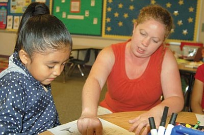 Ken Hedler/The Daily Courier<br /><br /><!-- 1upcrlf2 -->Breesa Patrick, right, a kindergarten teacher at Lake Valley Elementary School in Prescott Valley, coaches pupil Kasey Gaxiola, 5, on writing a letter to herself Wednesday, a day before the last day of school.