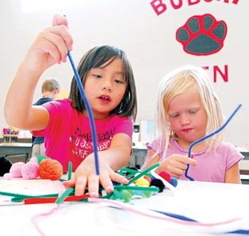 Matt Hinshaw/The Daily Courier<br> Katrina Nickle, 7, and Rachel Ashby, 6, work together on a project during arts and crafts at the Kids & Co. after-school program in Prescott.