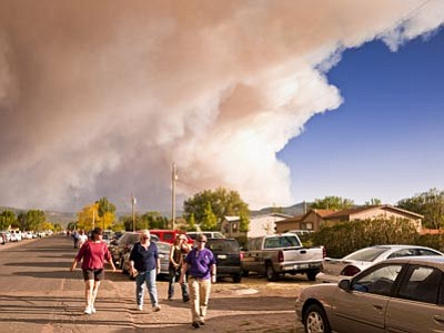Jack Kurtz/The Associated Press<br> A smoke column off the Wallow fire hovers over people on their way to a community meeting about the fire Friday in Springerville, Ariz.