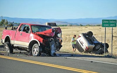 Matt Hinshaw/The Daily Courier<br>A member of the Chino Valley Police Department Accident Reconstruction Team inspects the scene of a double fatal car wreck on Highway 89 just south of Chino Valley Tuesday evening.