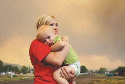 Marcio Jose Sanchez/The Associated Press<br>Emily Shupe comforts her 18-month-old  son Jax as the family prepares to evacuate to Phoenix as the Wallow Fire approaches in Springerville on Tuesday.