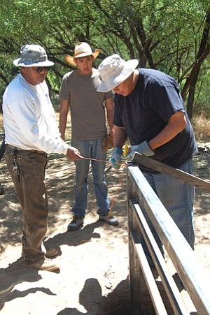 Joanna Dodder/The Daily Courier<br> College students Peter Danner and Joey Tapaha help BLM Engineering Technician Amos Sloan build a fence to protect the Agua Fria River in the Agua Fria National Monument.