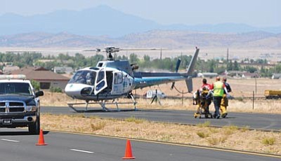 Les Stukenberg/The Daily Courier<br /><br /><!-- 1upcrlf2 -->Emergency personnel prepare to load Jonathan Jogerst, 20, of Prescott Valley onto a Flight for Life helicopter from a one-vehicle rollover on Glassford Hill between Long Look and Spouse in Prescott Valley Friday afternoon. The driver, 20-year-old Riley Litchfield of Prescott Valley, was killed in the rollover.