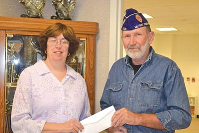 JCPenney manager Lisa Woodward presents a donation to Military Order of the Purple Heart Senior Vice Commander Mike Brody.