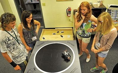 Matt Hinshaw/The Daily Courier<br> Left, Katie Duke, 14, and Stanley Swiacki, 15, watch as their sumobot battles Madalyn Markham, 14, and Tessa Diehl's, 15, sumobot during the Yavapai College Camp for Kids Robotics Workshop Saturday afternoon in Prescott.