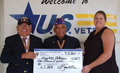 Lisa Irish/The Daily Courier<br>Frank Rodriguez, left, junior vice commander of the Military Order of the Purple Heart Chapter 608 donates $1,000 to help homeless veterans in our community during the Northern Arizona Veteran Stand Down to Skye Biasetti, right, operations manager for U.S. Vets, while Alfonso Santillan Jr., center, commander of the MOPH Chapter 608, looks on.